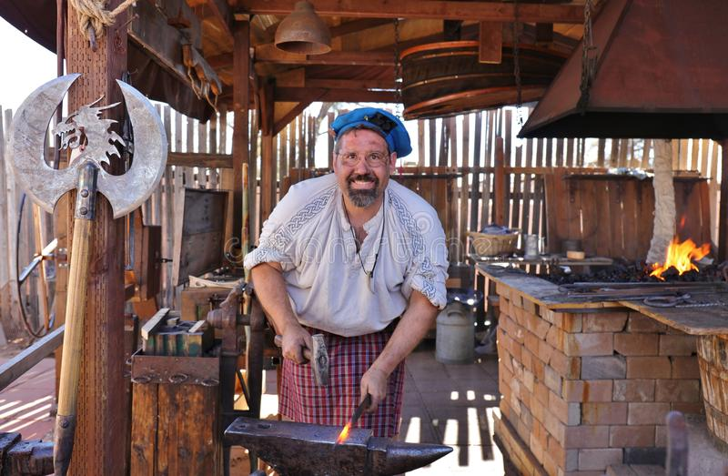 Blacksmith Forging Metal with Hammer. A blacksmith in traditional renaissance 14th to 17th century outfit forging red hot metal into a sword on an anvil with a stock photography