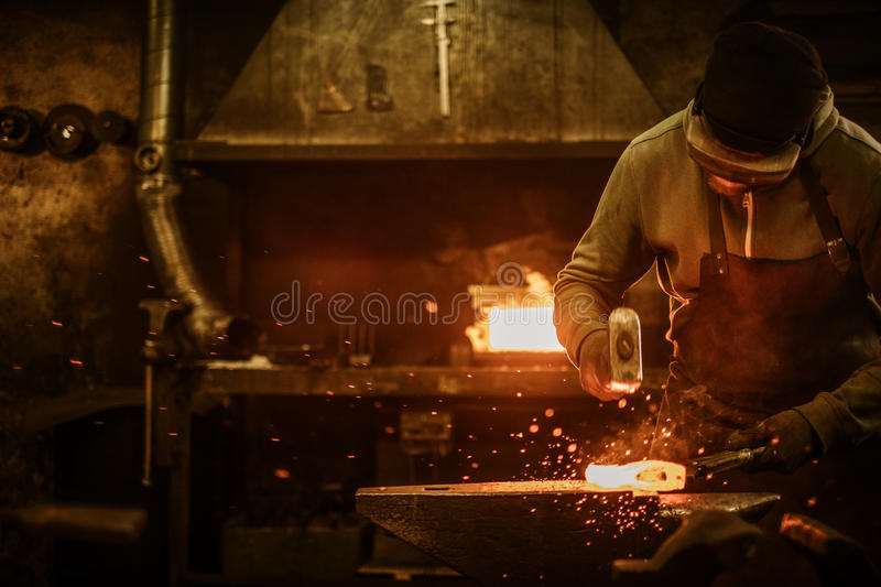 The blacksmith forging the molten metal on the anvil in smithy.  stock photo