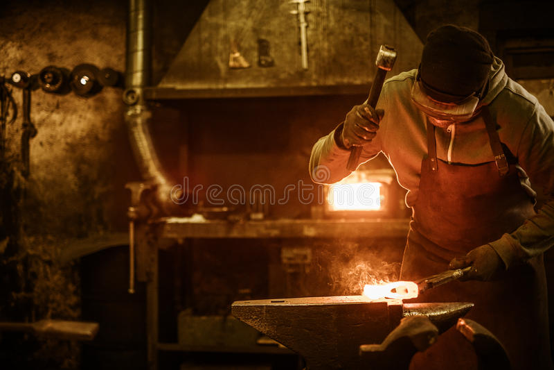 Blacksmith forging the molten metal on the anvil in smithy.  stock photos