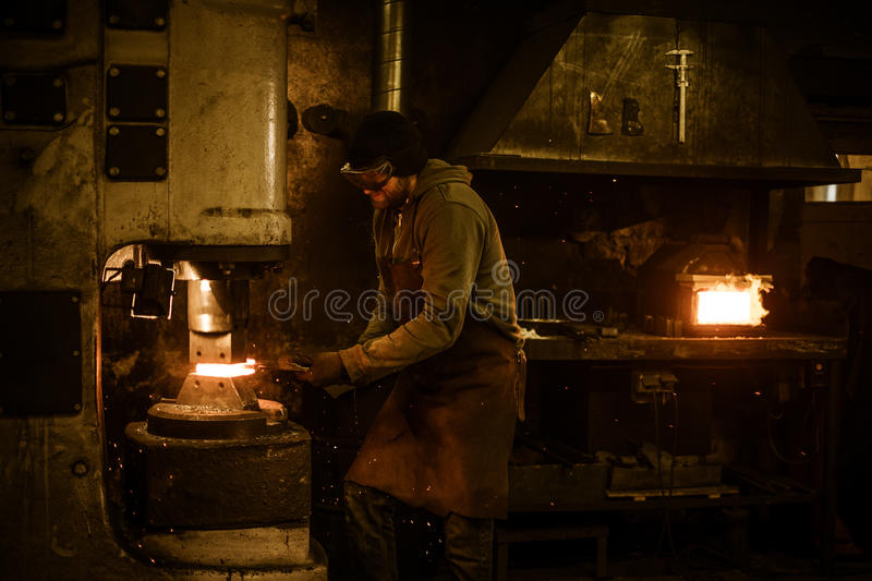 Blacksmith forging the molten metal on the power hammer in smithy.  royalty free stock images