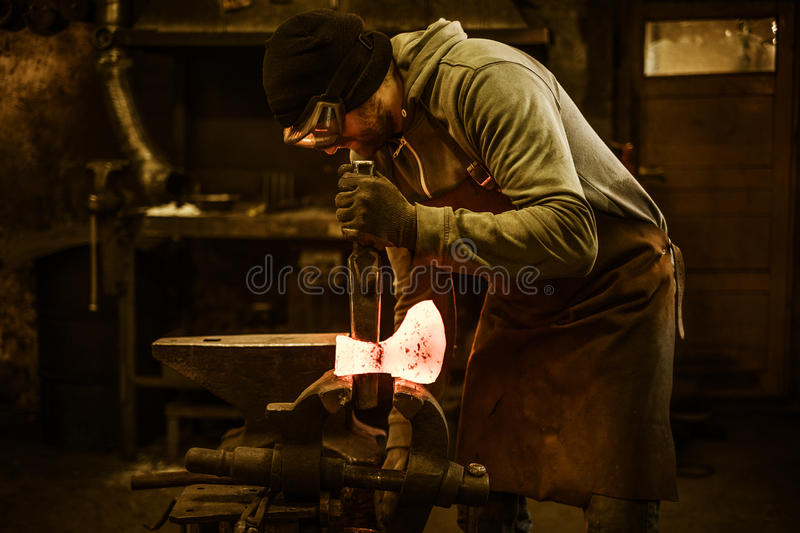 Blacksmith forging the molten metal on the rusty vise in smithy.  royalty free stock image