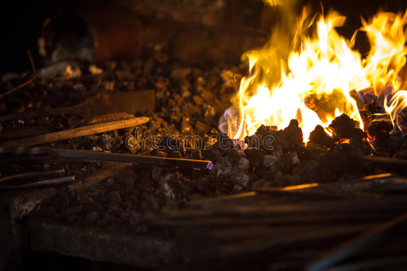 Blacksmith heating a metal rod. Coal forge heating a metal rod royalty free stock photo