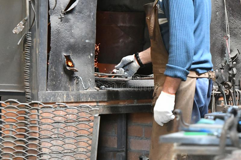 Blacksmith heats iron in a furnace. young traditional Blacksmith working with open fire The blacksmith making flames in smithy royalty free stock images