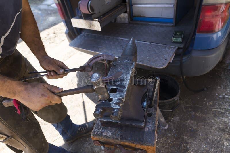 Blacksmith making horseshoes before the competition matches ridi. Thessloniki, Greece, June 14, 2015: Blacksmith making horseshoes before the competition matches stock image