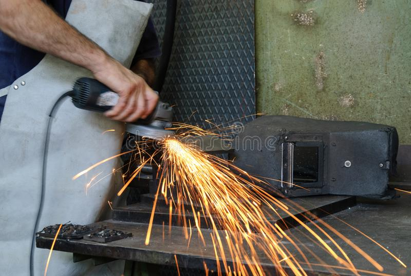 Blacksmith, a man smoothing iron with an emery. Blacksmith, a man at work in his laboratory smoothes iron with an emery royalty free stock images