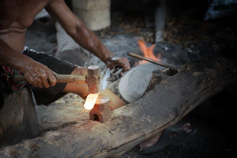 Blacksmith manually forging the molten metal on the anvil. Close up blacksmith manually forging the molten metal on the anvil royalty free stock photo