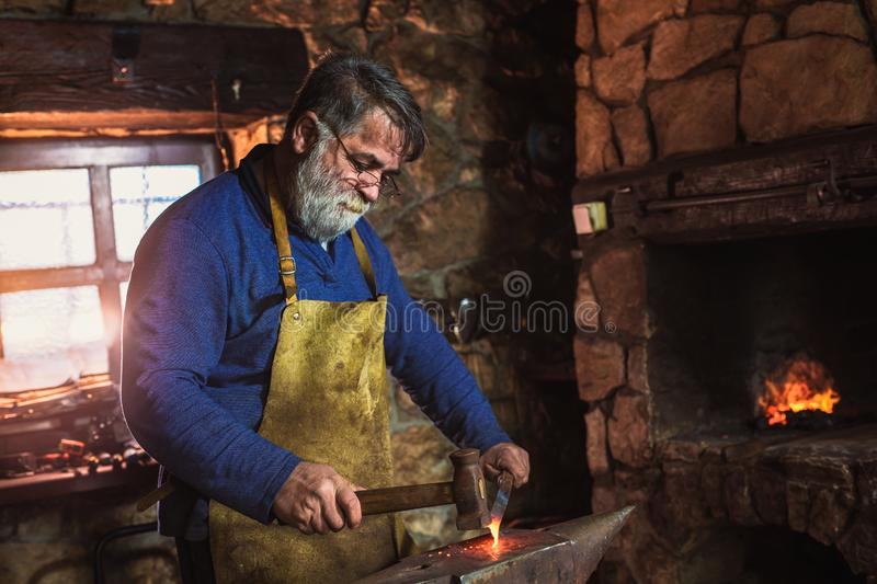 Blacksmith manually forging the molten metal on the anvil in smithy. With spark fireworks stock photo