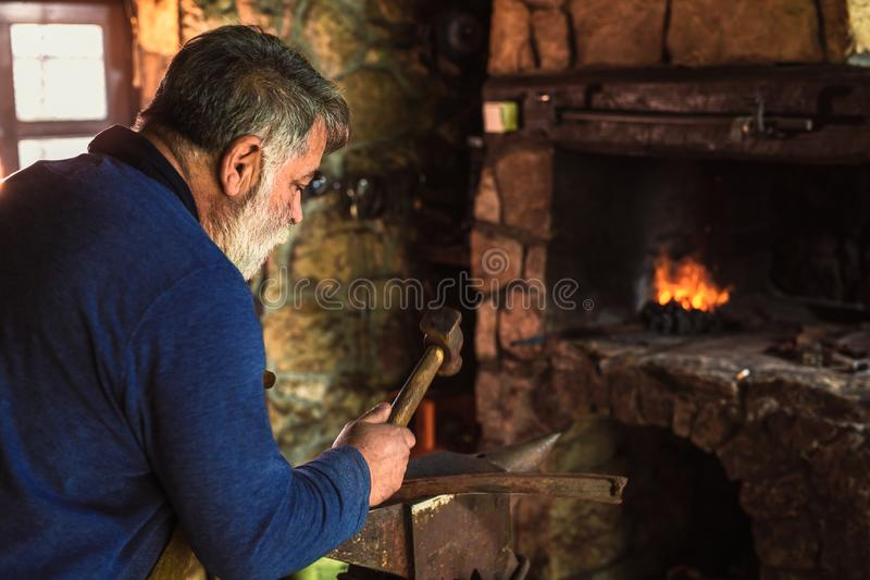 Blacksmith manually forging the molten metal. On the anvil in smithy with spark fireworks royalty free stock images
