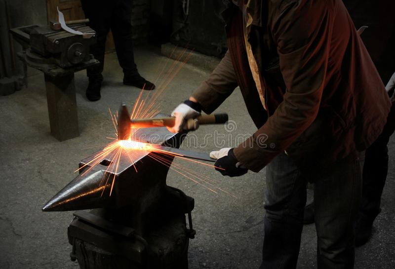 The blacksmith manually forging the molten metal on the anvil in smithy with spark fireworks. Spark. Dark background. stock photo