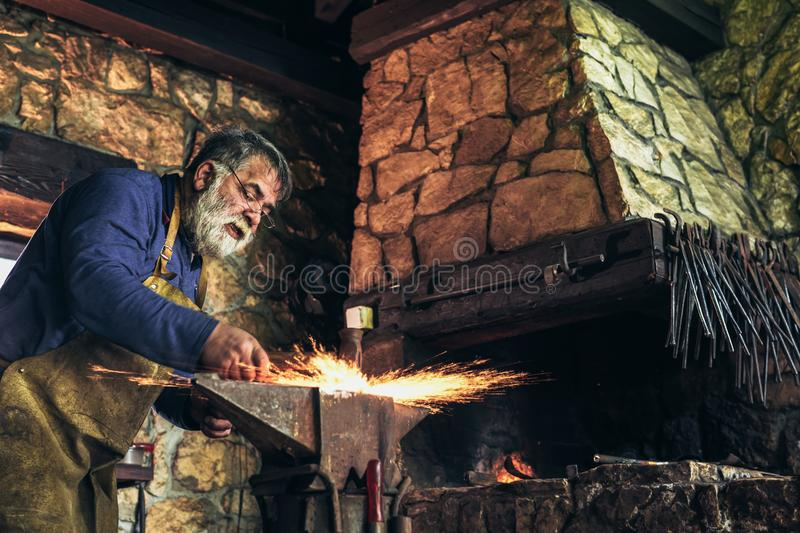 The blacksmith manually forging the molten metal. On the anvil in smithy with spark fireworks royalty free stock images