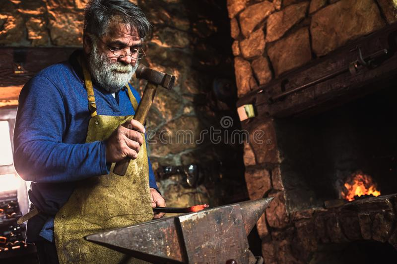 Blacksmith manually forging the molten metal. On the anvil in smithy with spark fireworks stock photography