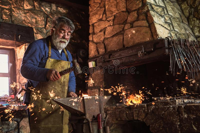 Blacksmith manually forging the molten metal. On the anvil in smithy with spark fireworks royalty free stock image