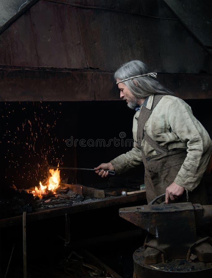 Blacksmith ogrzewa rzecz przed skuciem zdjęcie stock