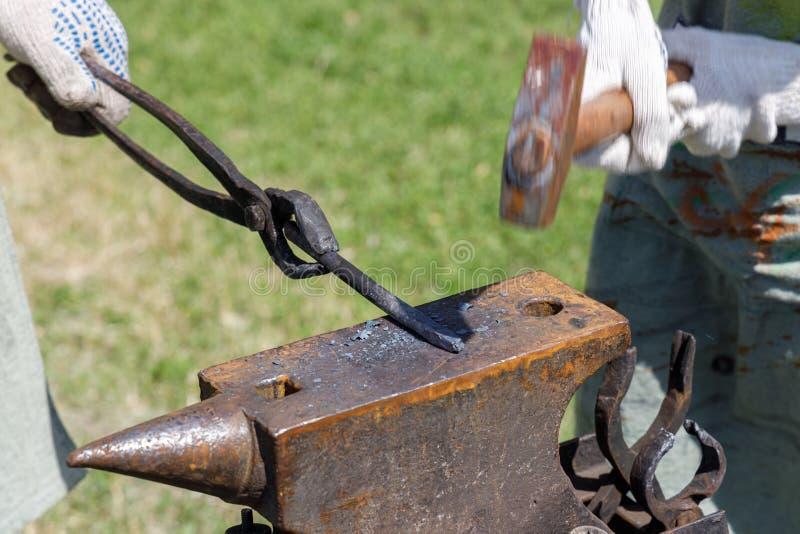 Blacksmith rhythmically hammering on a metal billet lying on the anvil.  royalty free stock photos