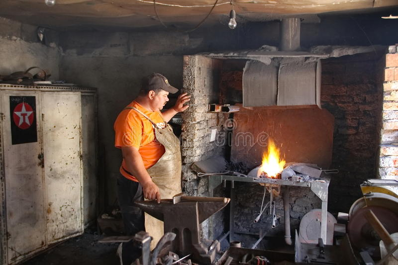 Blacksmith. In a small workroom waiting for the optimal temperature of fire. Photo taken on: July 26th, 2014 in Harghita county Romania royalty free stock photos