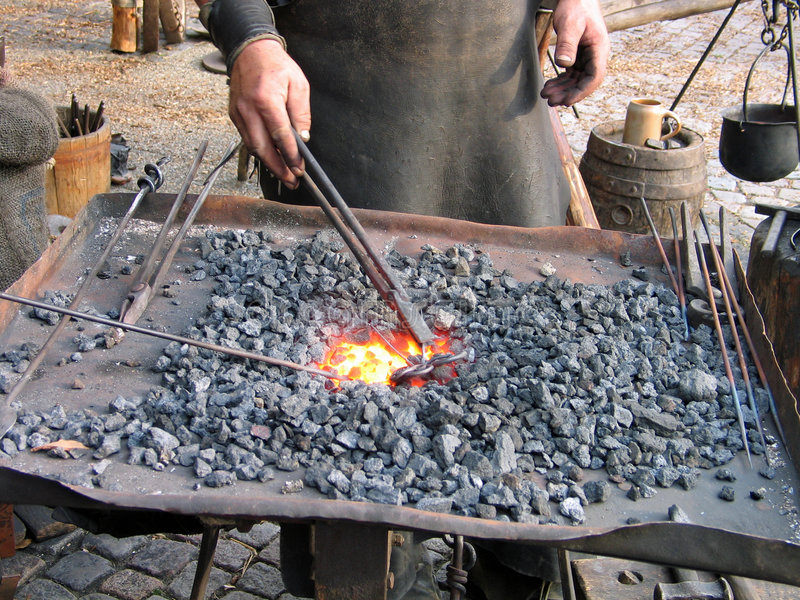 Blacksmith at work. In Medieval tradition stock photography