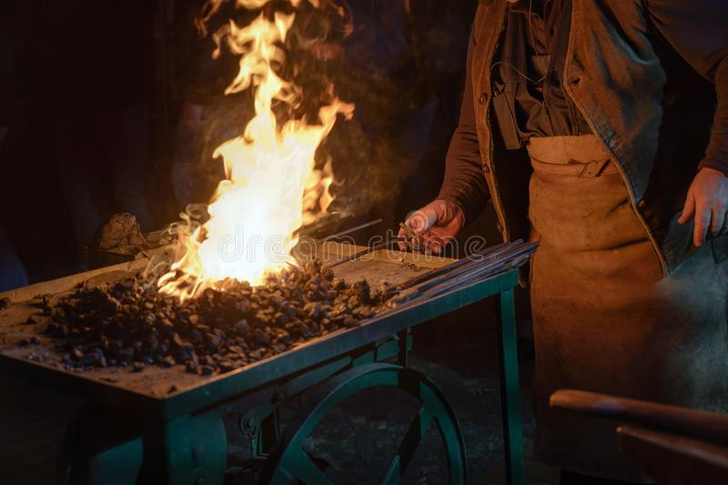 Blacksmith at work at the forge fire, working hands, some iron bars and the burning coal against a dark background stock images