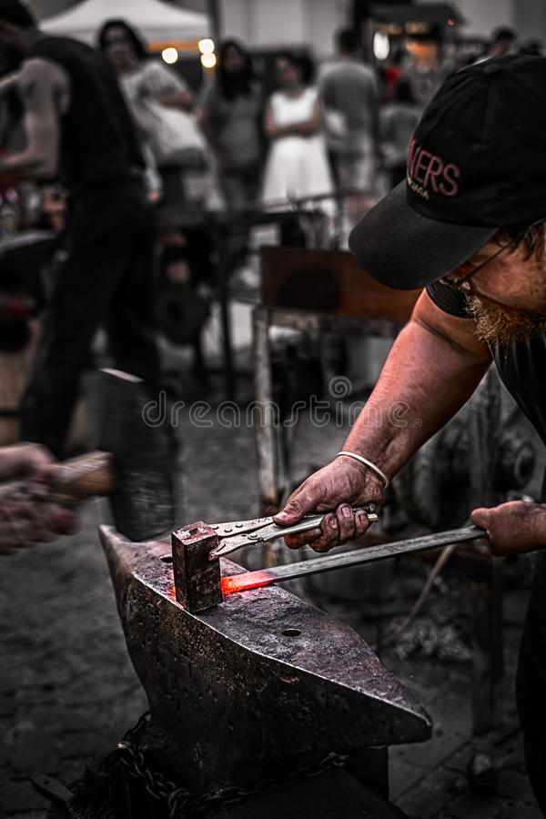 Blacksmith at work hitting the red iron stock images