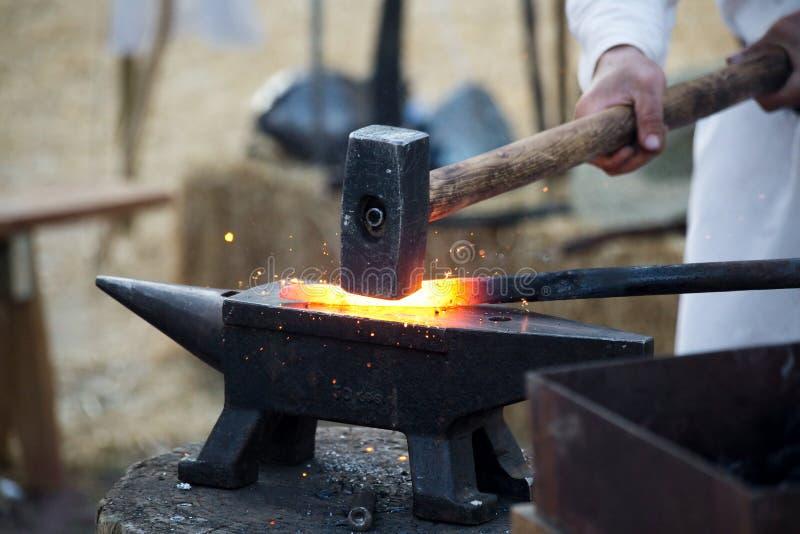 Blacksmith working hot iron royalty free stock images