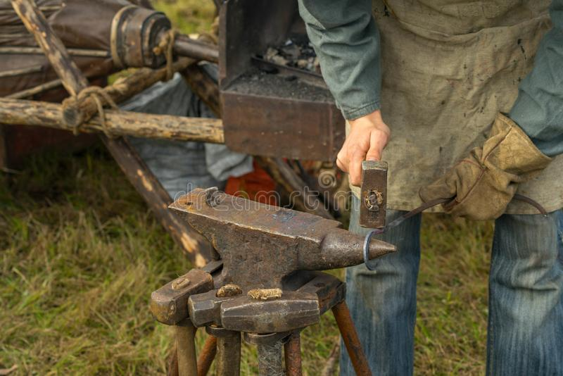 Blacksmith working at the anvil in the summer stock images