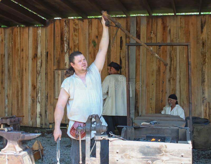 Blacksmith zasięg up to ciągną dźwignię działać bellows w staromodnym blacksmith sklepie przy Renassiance Faire Muskogee Oklahoma zdjęcie royalty free
