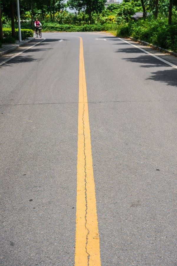 Blacktop con las líneas amarillas dobles divisor bajo sol fotografía de archivo
