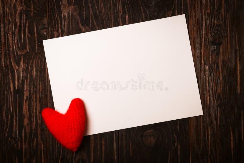 Blad en gebreid rood hart, de Dag van Valentine, bruine houten bac stock foto