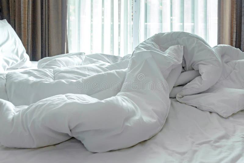Blad, het dekbed en het hoofdkussen van het matrasbed knoeiden het witte, omhoog in de ochtend in de bedruimte stock fotografie