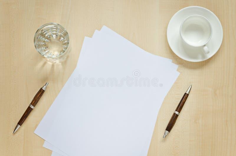 Blad van document, pennen, glas water en kop voor koffie stock foto's