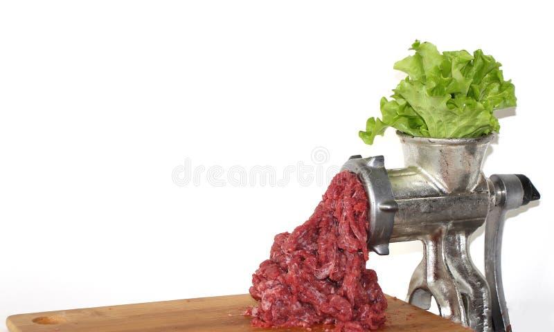 Bladbladeren in vleesmolen gemalen rundvlees komt uit de vleesmolen Gebouwd vleesconcept royalty-vrije stock foto's