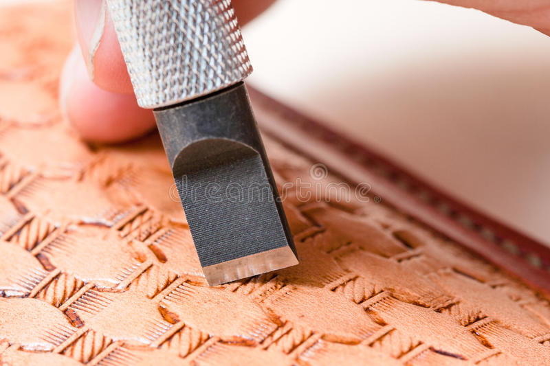Blade of swivel knife carving pattern on leather. Leathercrafting - blade of swivel knife carving pattern on leather close up stock images