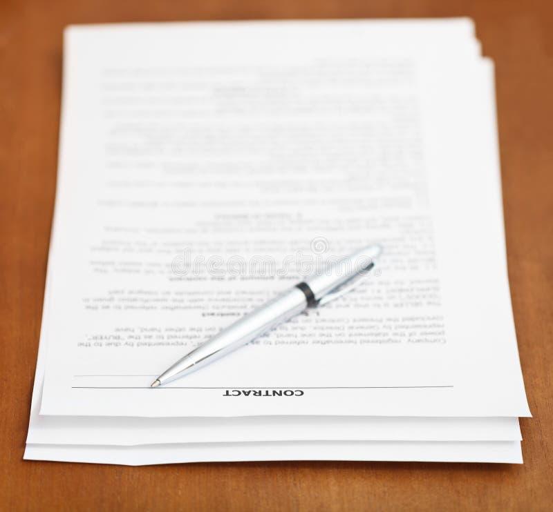 Bladen van contract en zilveren pen op houten lijst royalty-vrije stock afbeeldingen