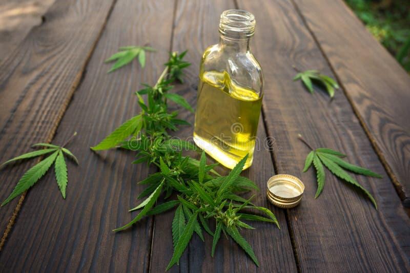 Bladeren van cannabis en fles met hennepolie op donkere houten surfa stock afbeeldingen