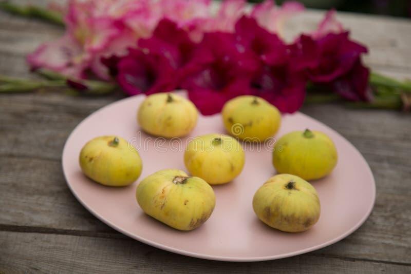 Bladożółte figi na różowią talerza z gladioluses zdjęcie stock