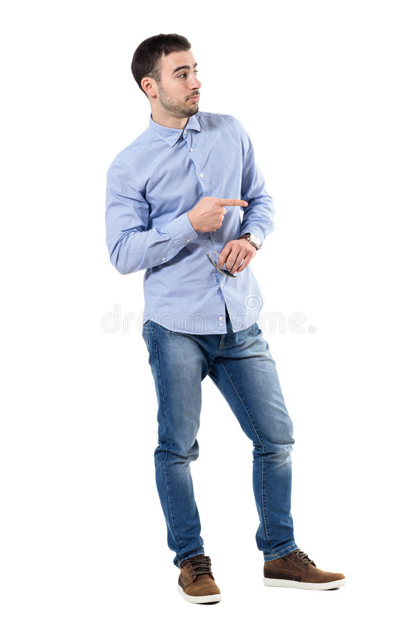 Blaming or accuse concept. Young businessman pointing finger looking away. Full body length portrait isolated over white background royalty free stock photo
