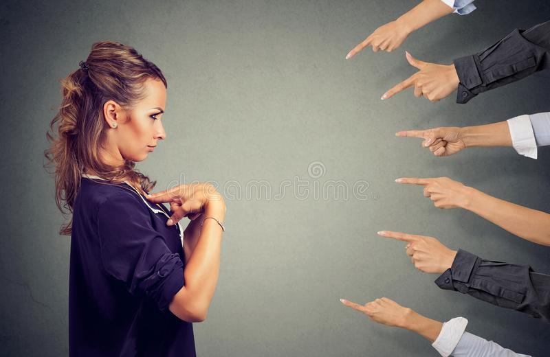 Blaming you. Anxious angry woman judged by different people pointing fingers hands at her. Negative human emotions face expression feeling royalty free stock photos