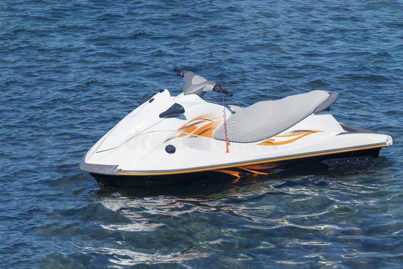 Blanc avec les flotteurs solitaires de scooter de l'eau de rayures oranges en mer bleue images stock