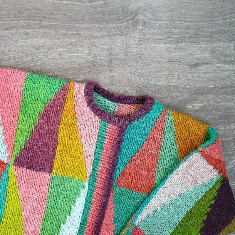 Blanc coloré, jaune, brun, rose, vert, bleu, turquoise, orange, cardigan tricoté fait main de laine de claret sur le backgroun en images libres de droits