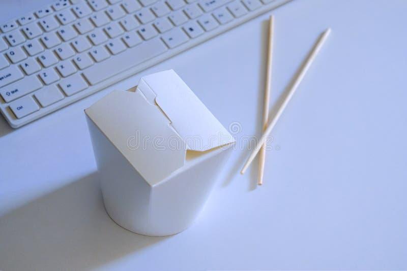 blanc Concept d'aliments de pr?paration rapide Une boîte avec la nourriture et les baguettes coréennes ou chinoises à côté d'un c photographie stock