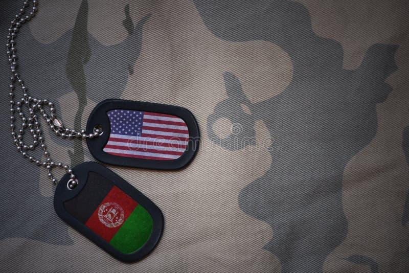 blanc d'armée, étiquette de chien avec le drapeau des Etats-Unis d'Amérique et l'Afghanistan sur le fond kaki de texture photo stock