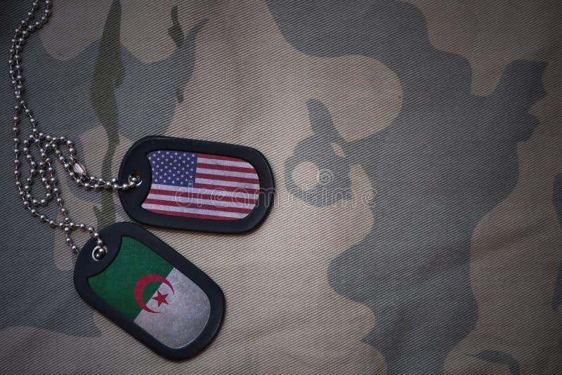 blanc d'armée, étiquette de chien avec le drapeau des Etats-Unis d'Amérique et l'Algérie sur le fond kaki de texture photos libres de droits