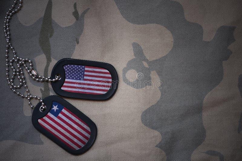blanc d'armée, étiquette de chien avec le drapeau des Etats-Unis d'Amérique et le Libéria sur le fond kaki de texture photographie stock libre de droits