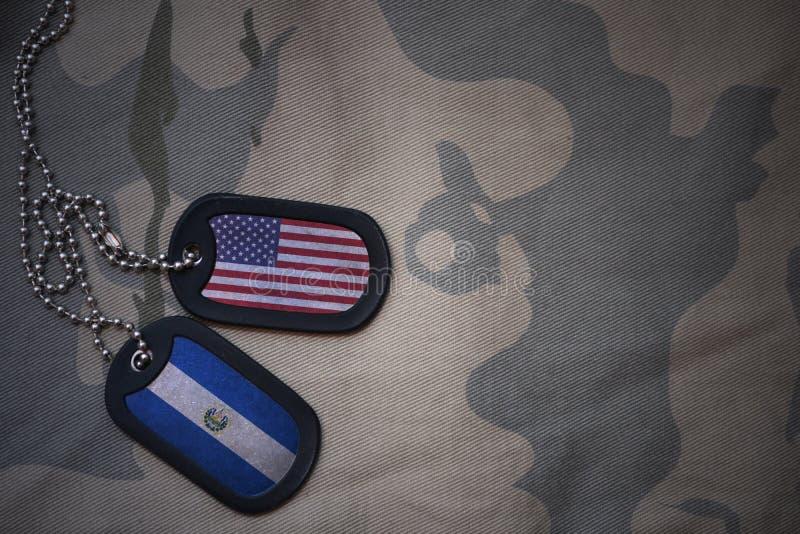 blanc d'armée, étiquette de chien avec le drapeau des Etats-Unis d'Amérique et le Salvador sur le fond kaki de texture photo stock