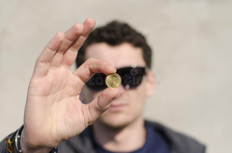 blanc d'homme d'isolement par main de pièce de monnaie photographie stock