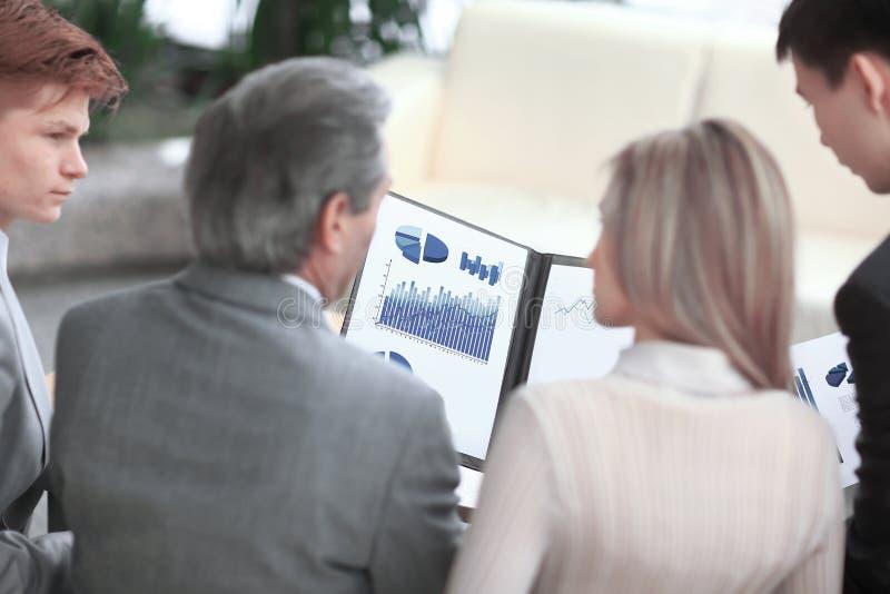 blanc d'isolement de vue arrière couples d'affaires discutant un diagramme financier photo libre de droits