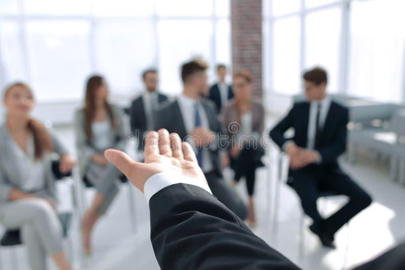 blanc d'isolement de vue arrière Entraîneur d'affaires faisant des gestes sa main devant un groupe de personnes images stock