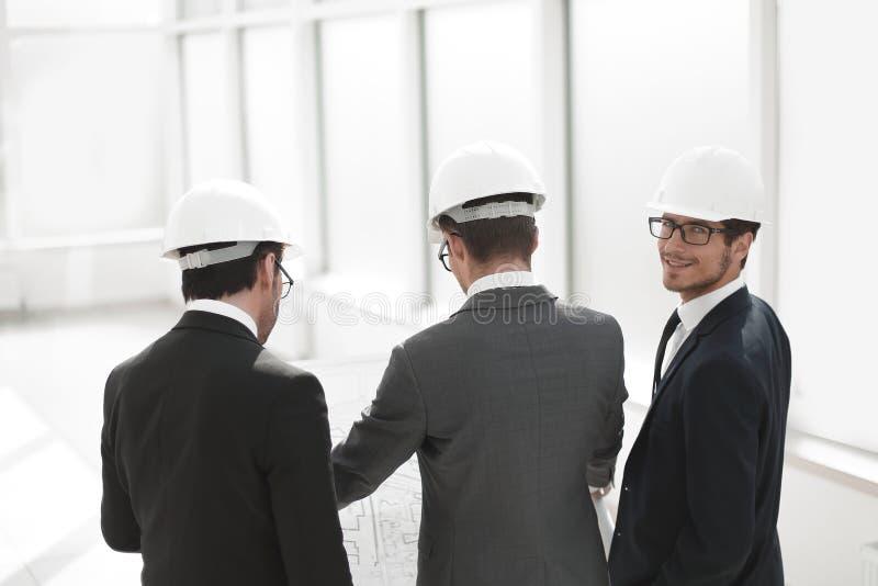 blanc d'isolement de vue arrière homme d'affaires et architectes se tenant dans le nouveau bureau images stock