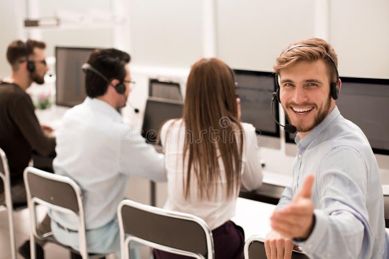 blanc d'isolement de vue arrière jeune agent de service client s'asseyant à son bureau photos libres de droits