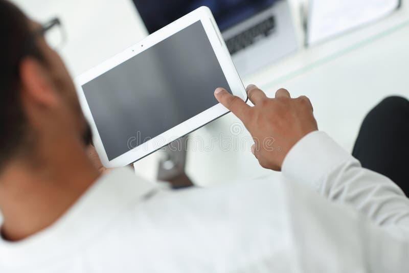 blanc d'isolement de vue arrière l'homme moderne utilise un comprimé numérique photo stock