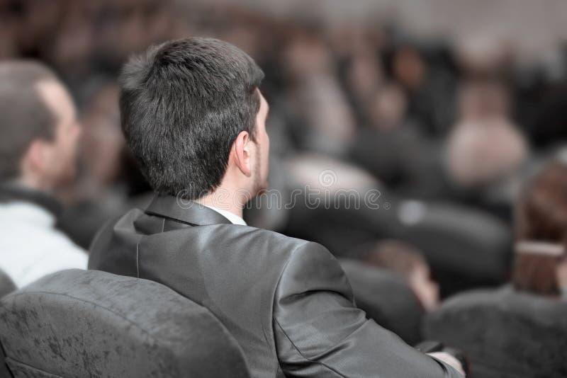 blanc d'isolement de vue arri?re les hommes d'affaires ?coutent le haut-parleur ? la pr?sentation d'affaires photos stock